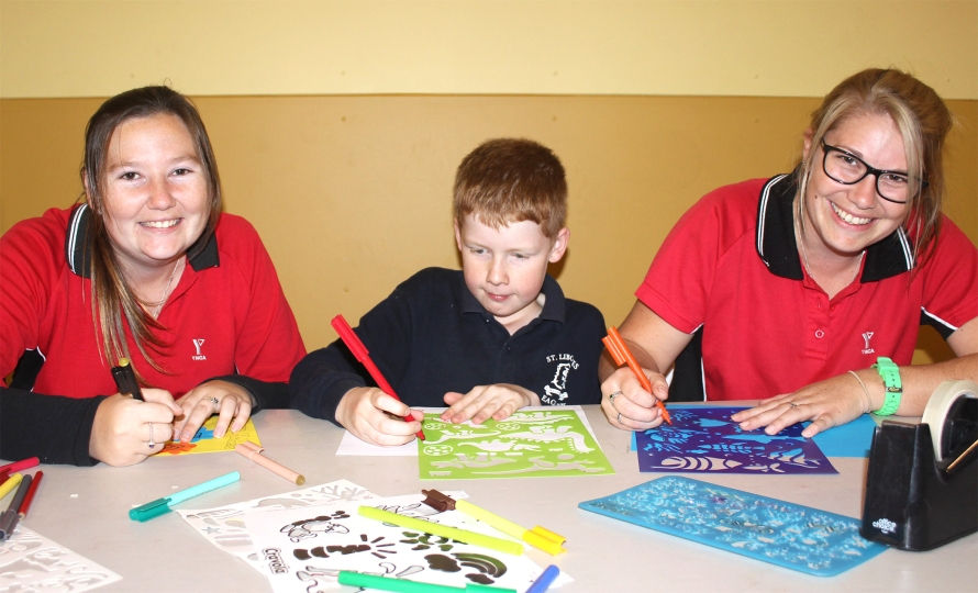 Education students Nerellie Dunn and Rhiannon Veal with after school care student Billy.